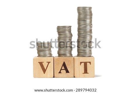 Growing taxes - wooden blocks with VAT and money stacks - stock photo