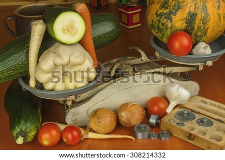 Growing vegetables in the organic farm. Vegetables grown in a small home garden. Old metal weight on homemade food. Background with vegetables. Promotion of healthy diets, diet food preparation. - stock photo