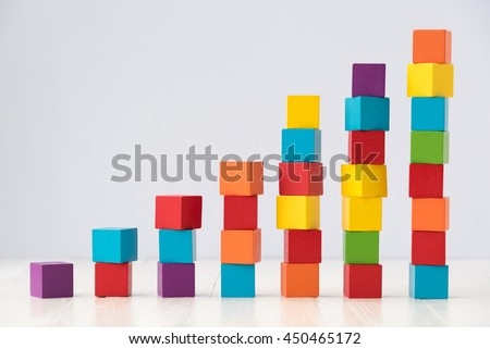 growning stack of colorful wood cube building blocks on white wood floor - stock photo
