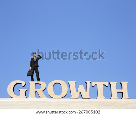 Growth business concept - business man stand on Growth text word and look sky, great for your design and business concept - stock photo