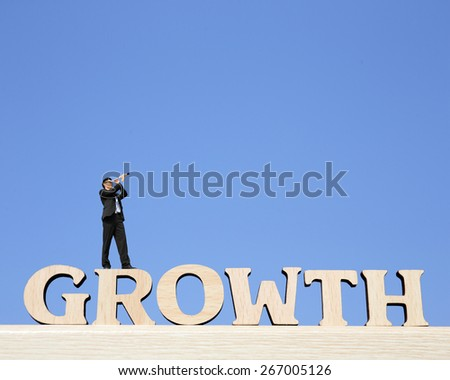 Growth business concept - business man stand on Growth text word with telescope ( spyglass ) and looking forward Prospects for future business - stock photo