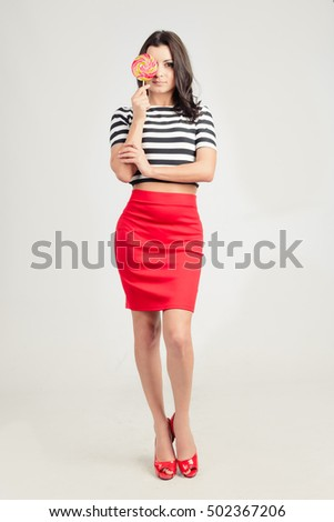 Growth portrait of a smiling brunette in a red short skirt, a striped top and red shoes with caramel (candy) in your hand. Mock up. Human