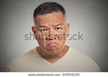 grumpy man isolated on grey wall background  - stock photo