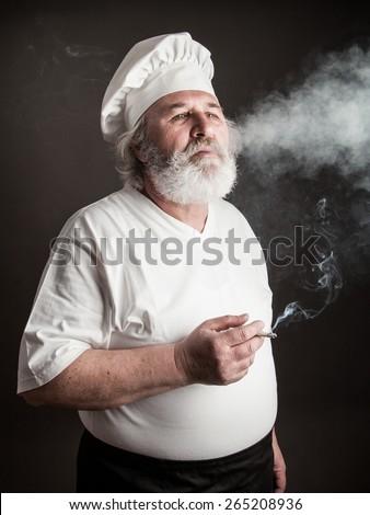 Grumpy old chef smoking against dark background - stock photo