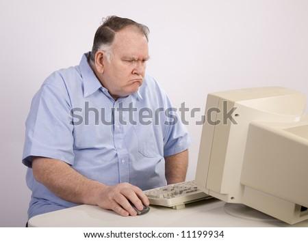 Grumpy old guy at computer - stock photo