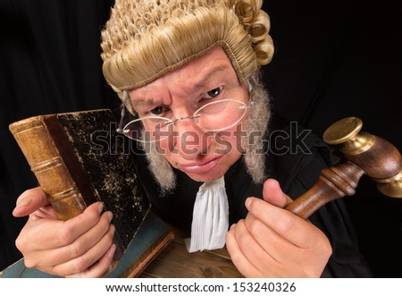 Grumpy old judge in extreme wide angle closeup with hammer and wig - stock photo