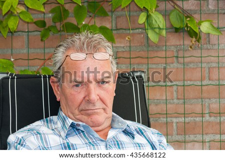Grumpy old man sitting outside in his garden with reading glasses on his forehead - stock photo