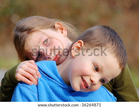 Grumpy sad big sister is holding onto smiling and content little brother in this cute sibling photo. - stock photo