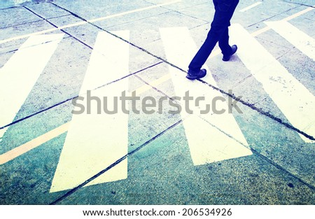 Grunge and vintage road crossing with pedestrian feet. Grunge and vintage filter effect used. - stock photo