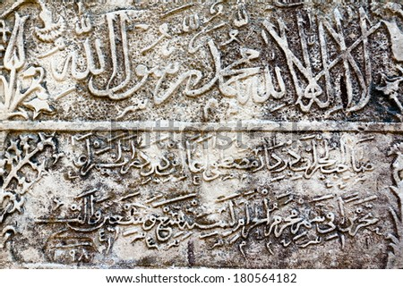 Grunge arabic inscription, relief on the wall - stock photo