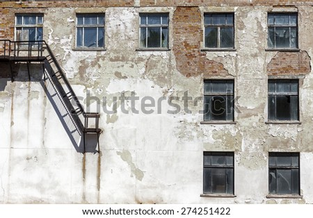 Grunge architecture details. Old abandoned factory with metal staircase and broken windows - stock photo