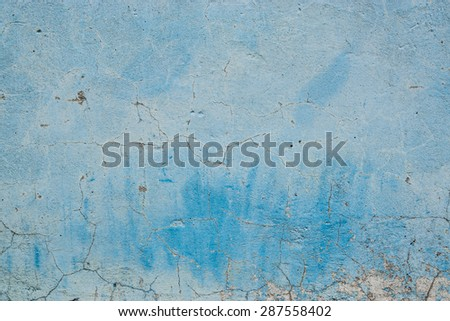 Grunge Background. Wall with the blue colored whitewash falling off fragment with clacks as a background texture - stock photo