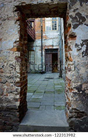Grunge dark alley, slums of the city, squalid dirty corner of street in the decadent old town - stock photo