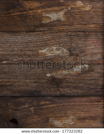 Grunge dark wood background with pieces glued paper on it - stock photo