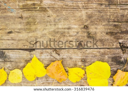 Grunge dark wooden background with old rough timber and some yellow autumn leaves on it. Rustic style - stock photo