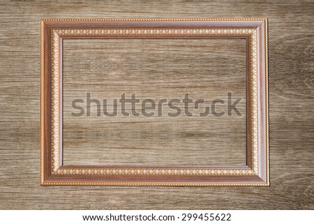 Grunge gold wooden frame on the wooden wall