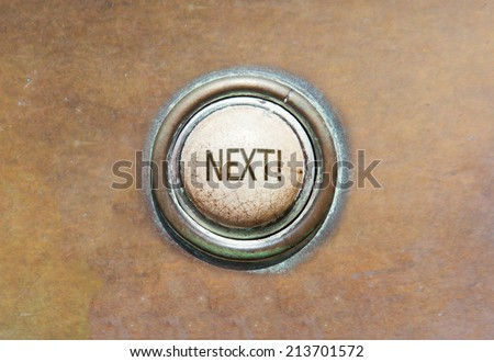 Grunge image of an old button - next! - stock photo
