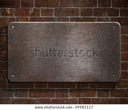 grunge metal plate with rivets on brick wall background - stock photo
