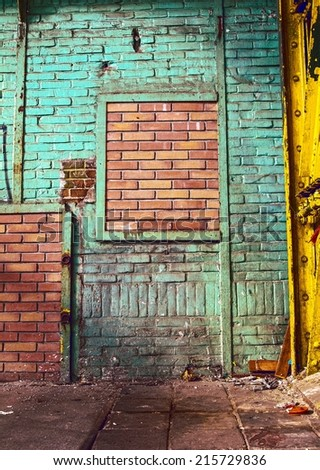 Grunge, old and dirty building interior . Green painted  worn brick wall with deeply detailed and clean brick wall inside like a frame. Contrast abstract background.  - stock photo