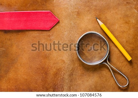 Grunge old leather with magnifying glass and pencil - stock photo