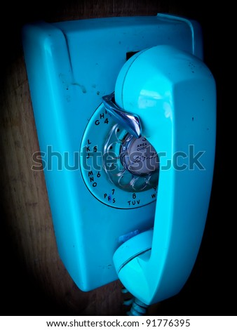 Grunge old phone seen in a coffee shop mounted near the floor for children to play with. - stock photo