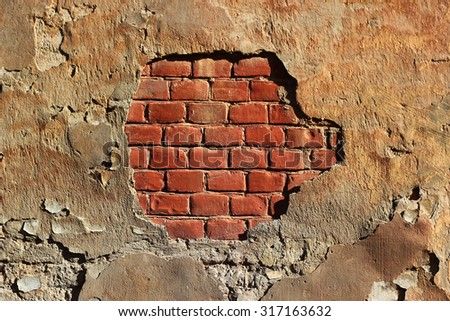 Grunge painted red brick wall background texture with weathered damaged pitted concrete and peeling plaster and ochre colored paint - stock photo