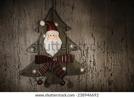 Grunge photo of Christmastime decoration, decorative wooden Christmas tree with Santa Claus ornament, happy New Year, holiday greeting card, home ornate, retro style image, xmas background  - stock photo