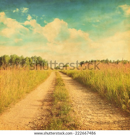 Grunge photo of rural road in the grass field. - stock photo