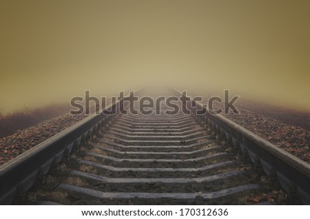 grunge railroad to horizon in fog - stock photo