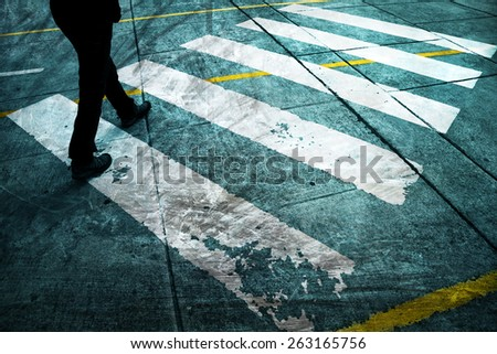 Grunge road crossing with pedestrian feet. Blue color tone added. - stock photo