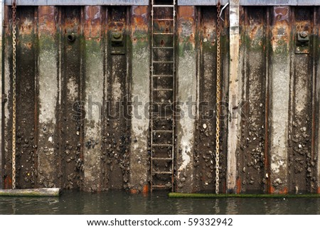 Grunge rusted metal surface wall in a harbor close to the water. - stock photo