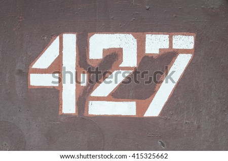 grunge rusty metal background with chipped and cracked paint and the number four hundred twenty-seven