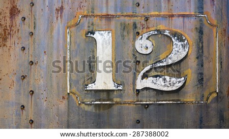 grunge rusty steampunk metal background with faded painted number twelve - stock photo