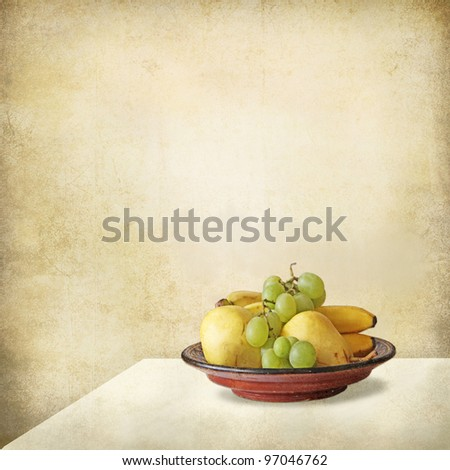 Grunge still life of a light interior, a table and a fruit tray - stock photo