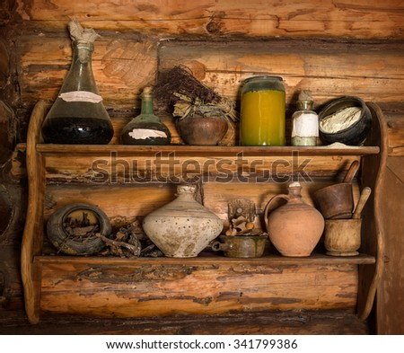 Grunge storage cupboard in hut with corked ink vial, poison phial, dry herb bunch, oil, scattered flour, jam and liqueur in jug with label for title. Closeup view with space for text on brown bar wall - stock photo