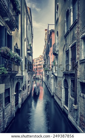 Grunge style photo of an old narrow Venetian street, beautiful aged buildings over water canal, romantic destination, Venice, Italy - stock photo
