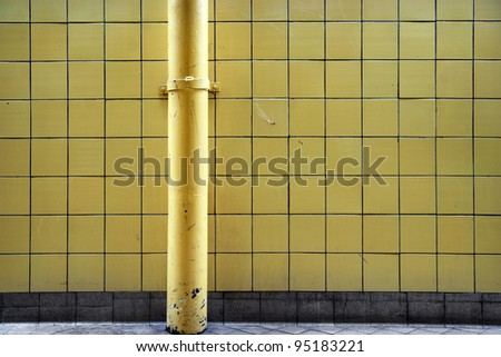 grunge tiled wall with painted metal pipe