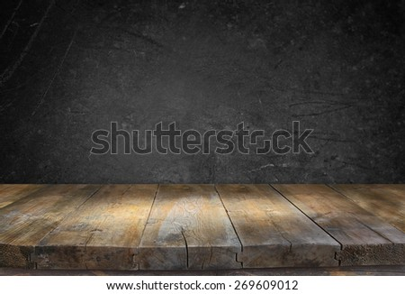 Grunge vintage wooden board table in front of black textured background - stock photo