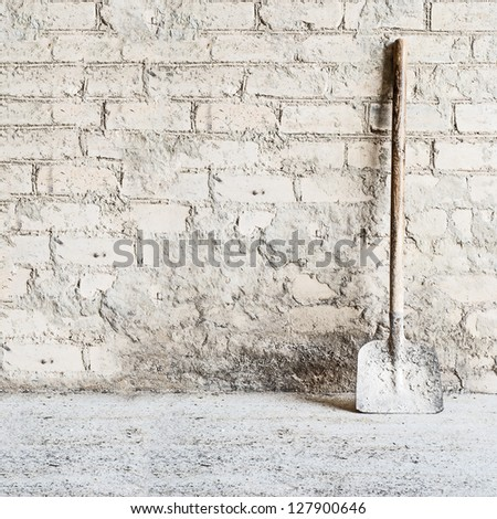 grunge wall background at the mill, shovel near the wall - stock photo