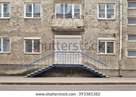 Grunge weathered house  with some windows, grunge folding door, rain pipe - stock photo