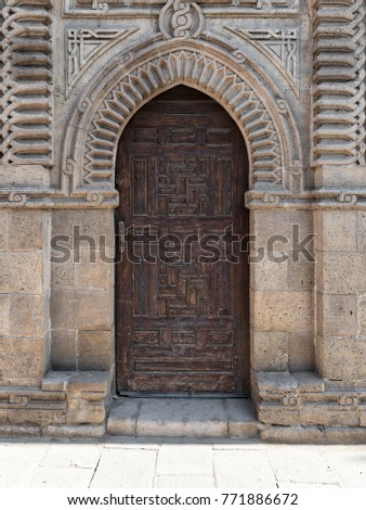Grunge wooden ornate aged vaulted arched door on exterior decorated stone bricks wall at Manial Palace of prince Mohamed Ali, Medieval Cairo, Egypt