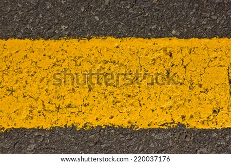 Grunge yellow paint line on asphalt.