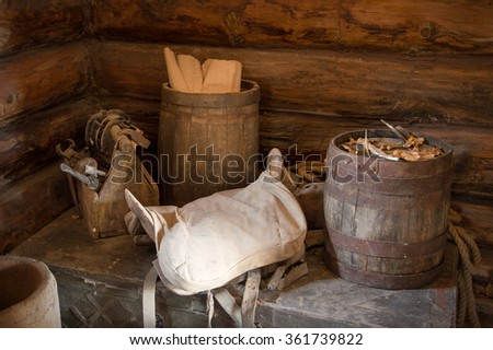 Grungy aged country style storage used oak tun barel, worn horse seat, supply items making store on dusty chest in board shed. Closeup view with space for text on dark brown bar wall cottage backdrop - stock photo