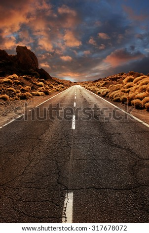 Grungy asphalt road leading through desert sunset landscape - stock photo