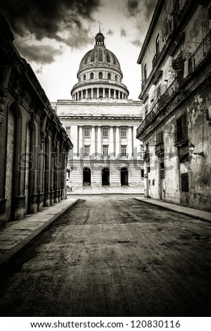 Grungy black and white image of a street with crumbling buildings leading to the Capitol in Old Havana - stock photo