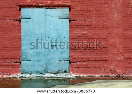 Grungy blue door on a worn red brick wall - stock photo
