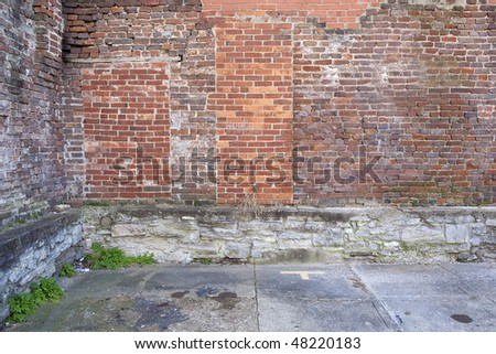 grungy brick wall parking lot - stock photo