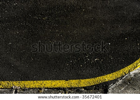 grungy, dirty view of asphalt with distinct curved yellow stripe