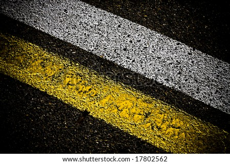 grungy, dirty view of asphalt with distinct yellow and white stripes - stock photo
