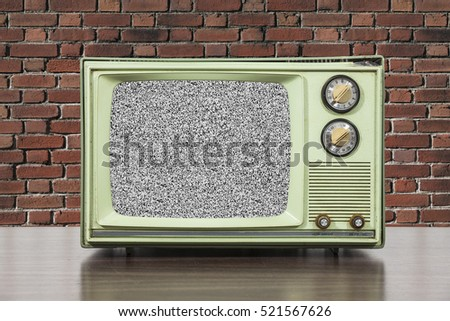 Grungy green vintage television set with brick wall and static screen.